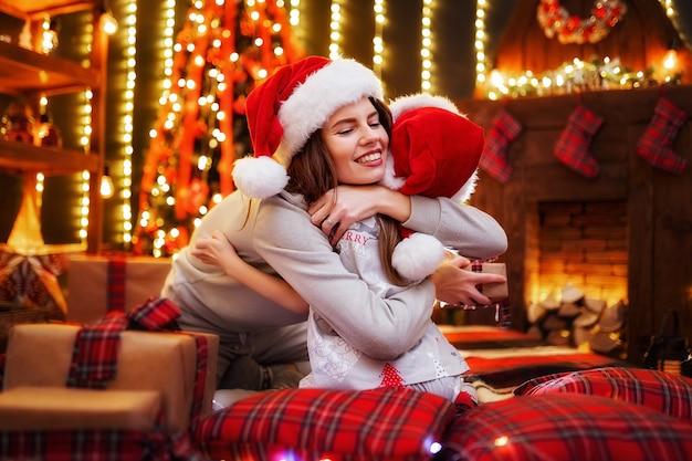 Веселая мама и ее милая дочь девушка обменивается подарками. родители и маленькие дети веселятся возле дерева в помещении. любящая семья с подарками в комнате рождества.