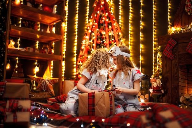 クリスマスパジャマを着て幸せな女の子は、クリスマスイブに居心地の良い暗いリビングルームの暖炉のそばでギフトボックスを開きます。