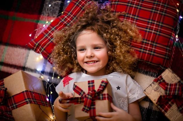 ギフトボックスを保持している休日クリスマスパジャマで笑顔のかわいい小さな子供の肖像画。上面図。