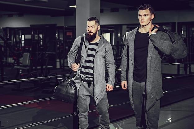 Уверенные молодые спортсмены выходят из спортзала