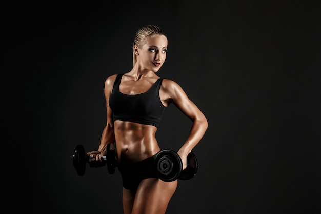 ダンベルを持つ性的な女性のトレーニング