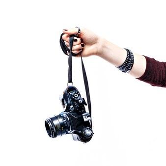 Рука женщины держа старую камеру изолированный