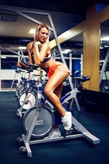 モダンなフィットネスセンターで自転車で運動フィットネス女性