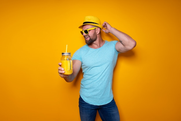 明るいオレンジ色の飲み物でポーズの男