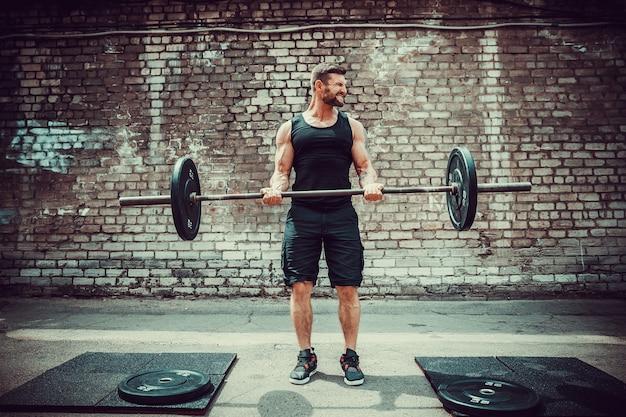 Спортивный человек, работающий со штангой. сила и мотивация. бицепс упражнений.