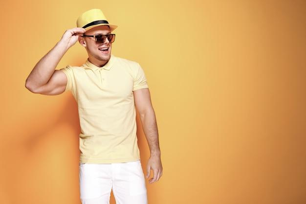 黄色のシャツ、サングラス、白いパンツ、麦わら帽子で自信を持ってスタイリッシュな男