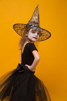 Малая девушка в костюме ведьмы хеллоуина, оранжевой поверхности.