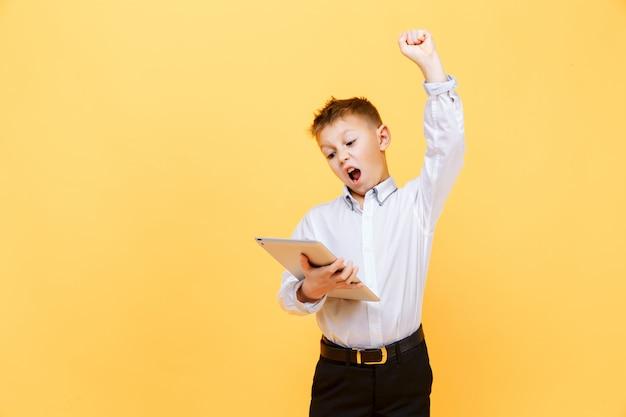 タブレットを使用してフォーマルな服装で幸せな少年。スタジオショットに分離された黄色。勝者。