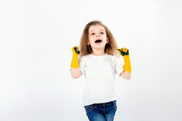 Очаровательная маленькая девочка, современная прическа, белая рубашка, синие джинсы, крик, рев, улыбка