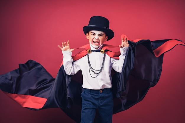 Хэллоуин-мальчик-вампир машет руками черным, красным плащом