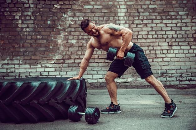 Спортивная (ый) человек работает с гантелями. сила и мотивация. упражнения для мышц спины
