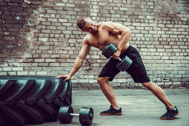 ダンベルでワークアウト運動の男。強さと動機。背中の筋肉の運動
