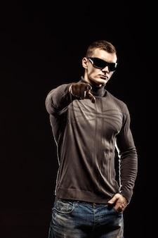 Портрет молодого человека указывает пальцем на черном фоне