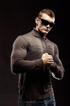 Боевой мускулистый герой боевик в коричневом свитере и солнцезащитных очках