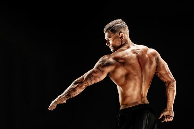 暗いシーンにフィットネス筋肉男のポーズのボディービルダー