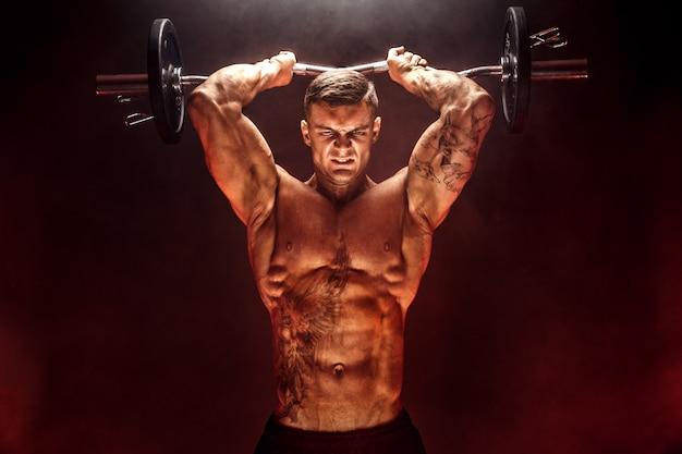 Сильный спортсмен поднимая тяжелую гантель в дыму