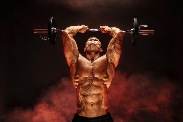 赤い煙でダンベルを持ち上げる筋肉の男の肖像上腕三頭筋の運動