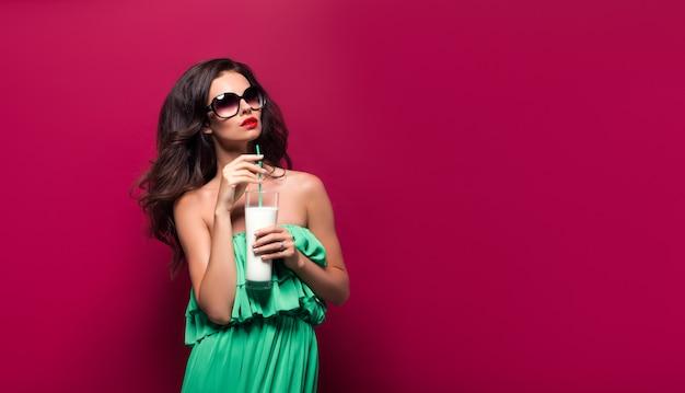 サングラスと赤いシーンでカクテルと緑のドレスの美しい若いブルネットの肖像画。孤立した