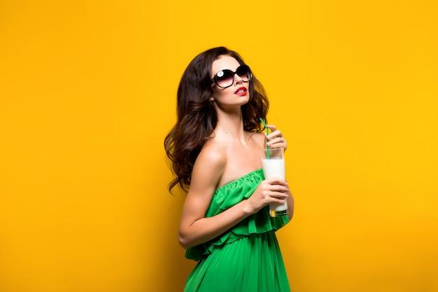 カクテルと緑のドレスでブルネットのスタジオ撮影