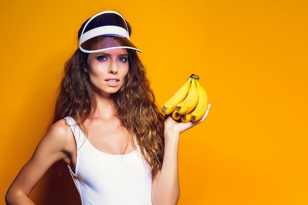 水着とバナナを押しながらポーズを黄色のシーンで分離された青いショートパンツの女性