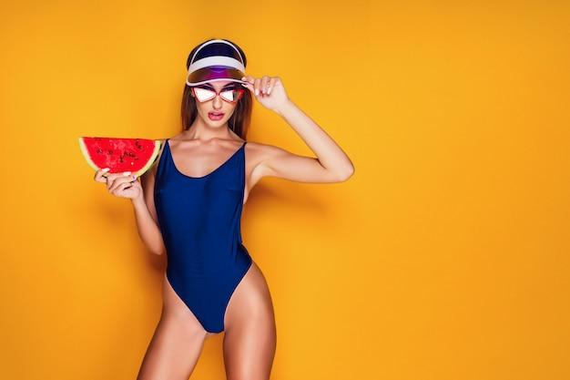 Женщина в кепке и купальниках держит кусочек арбуза