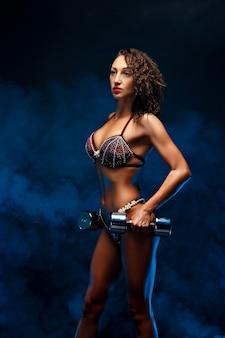 Красивая фитнес женщина подъема гантелей.