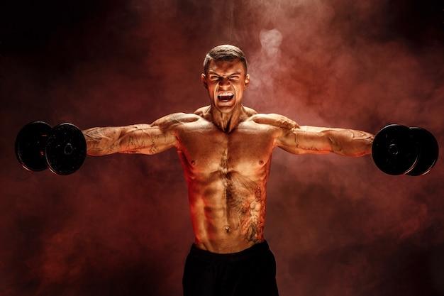 Очень мускулистый парень, культурист, выполняющий упражнение с гантелями, на