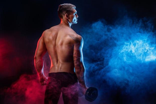 ダンベルで運動をしている筋肉の男を集中