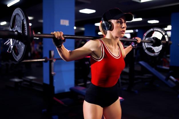 Красивая спортивная сексуальная женщина в кепке и наушниках делает приседания в тренажерном зале