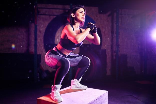 クロスフィットスタイルでジャンプボックスをやって魅力的なフィット中年女性。女性アスリートはジムでジャンプを実行しています