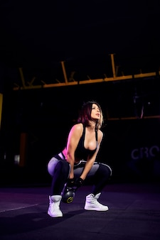 Привлекательный подходит женщина среднего возраста спортсмен выполняя качели чайника в тренажерном зале