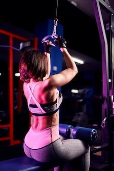 ジム-背面図で、マシンを使用して背中の運動を行う運動の女性