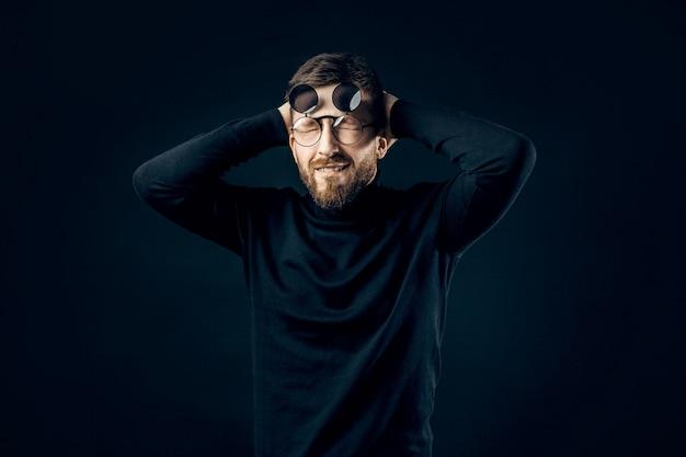 Удивленный бородатый мужчина в черных округлых очках держит голову
