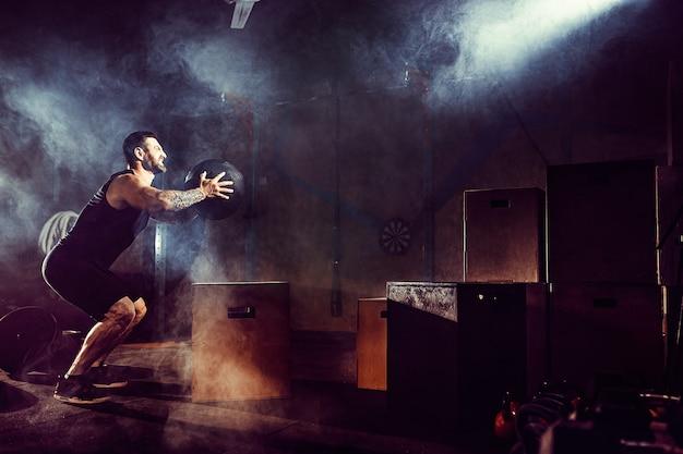 運動選手は運動をしました。ボックスにジャンプします。フェーズタッチダウン。暗いトーンのジムショット。ジムで煙します。