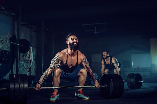 Два мускулистых бородатых татуированных спортсмена тренируются в спортзале