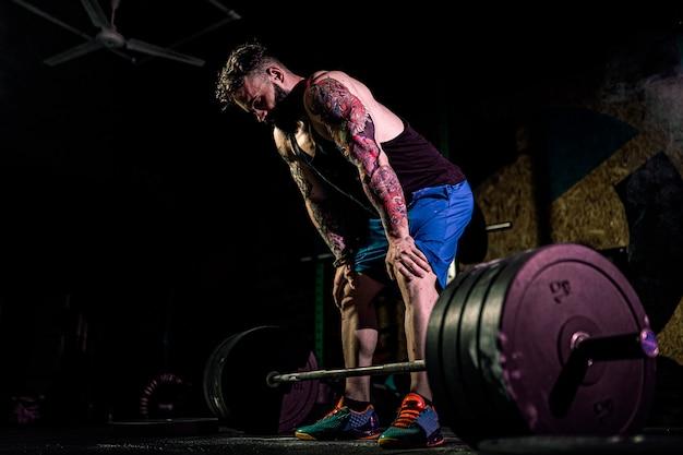 モダンなフィットネスセンターでバーベルのデッドリフトを準備する筋肉フィットネス男。機能トレーニング。