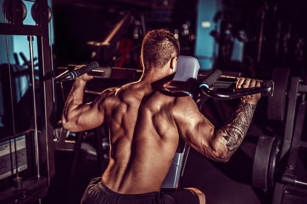 ジムでトレーニングマシンの肩の平均デルタのダンベルで激しい運動をしている筋肉青年
