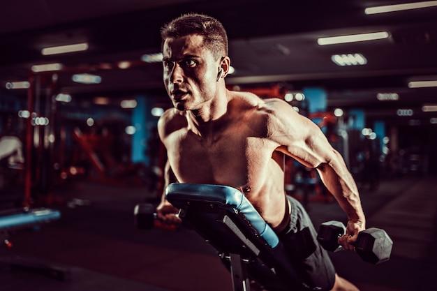 Молодой мускулистый мужчина делает тяжелые упражнения с гантелями для задних дельт плеч на тренировочной скамье в тренажерном зале