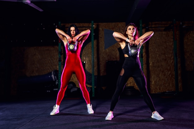 Два привлекательных подходят женщины спортсмен выполняет качели чайник в тренажерном зале