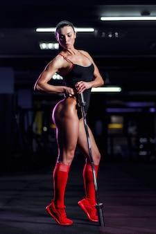 運動とジムでバーベルでポーズフィットネス女の子