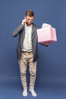 Вскользь человек держа розовую обернутую коробку