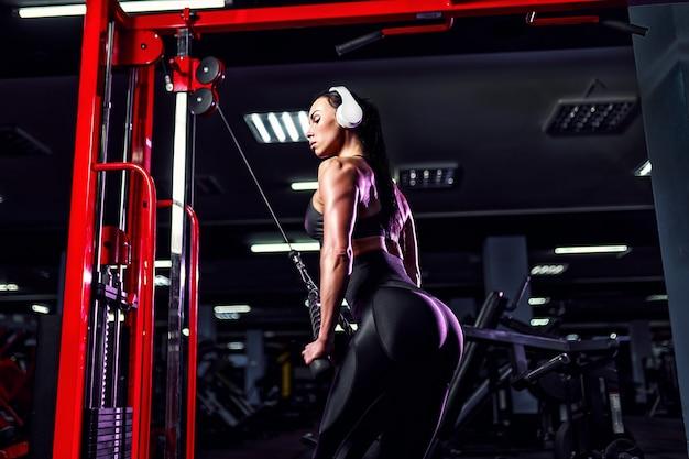 Атлетическая сексуальная женщина делая тренировку используя машину в спортзале - взгляд со стороны