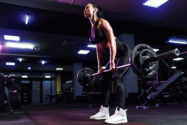 Привлекательная подходит сексуальная женщина в спортзале приседает со штангой. тренировка женщины назад