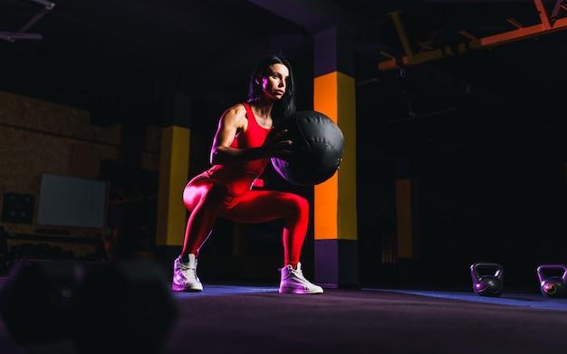 フィットネスボールでスクワット運動を行うスポーツウーマン。女性運動とジムで薬のボールでストレッチ