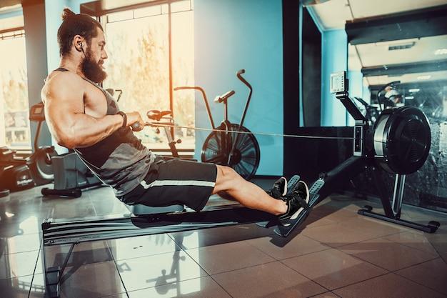 Мускулистый мужчина с гребной тренажер в тренажерном зале