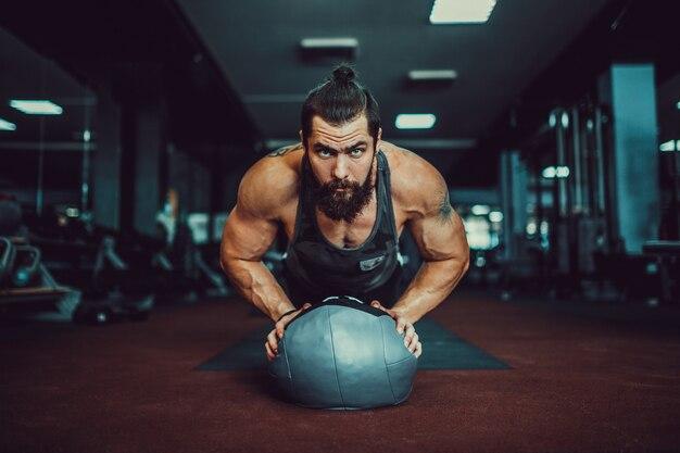 筋肉質の若い男がスポーツウェアを着用し、ロフトのインテリアの床で運動しながら板の位置を行う