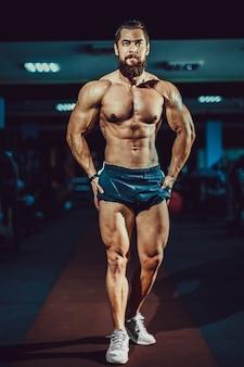 ジムでポーズをとって運動筋肉ボディービルダー男。