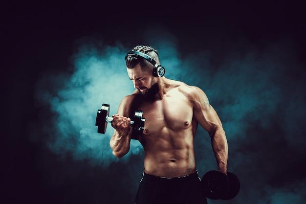 男は煙で暗い背景にスタジオでダンベルで筋肉をトレーニングします。