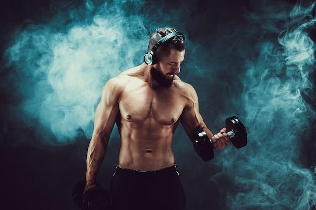 Укомплектуйте личным составом тренировки мышц с гантелями в студии на темной предпосылке с дымом.