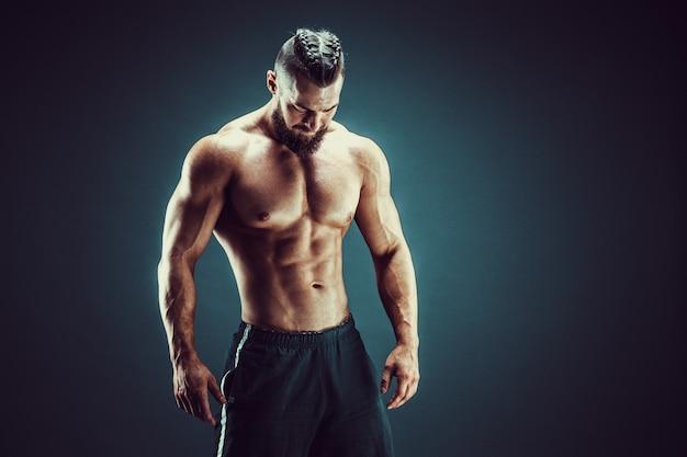 ボディービルダーのポーズ。暗い背景にフィットネス筋肉男。